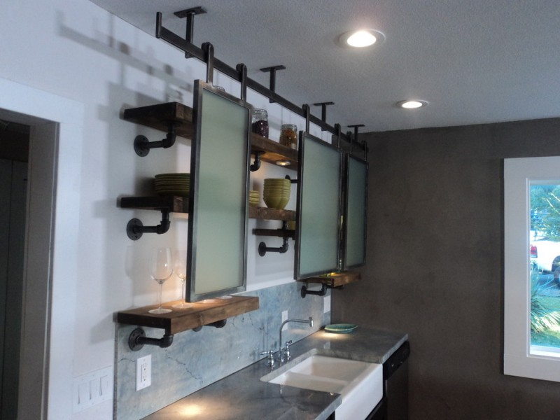eclectic kitchen with vintage modern industrial kitchen shelves concrete countertop double white sinks Stucco walls