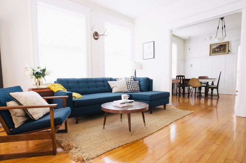 eclectic living room idea blue couch with chaise blue chair round top coffee table in vintage style woodboard floors white walls