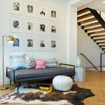 Entryway Living Room Idea Single Industrial Sofa Multicolored Pillows White Ottoman Chair Cowhide Area Rug Medium Toned Wood Floors White Walls With Decorative Framed Photographs
