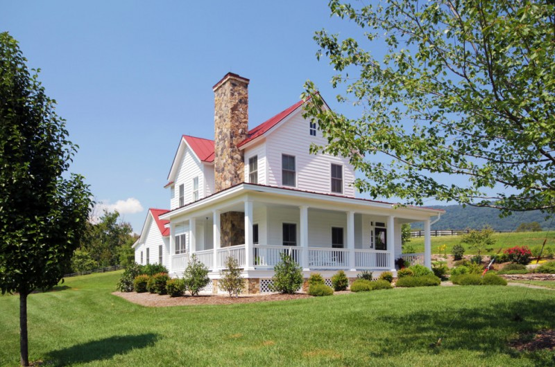 farm style house plans covered front porch red metal roof standing seam metal roof white clapboard siding stone face chimney