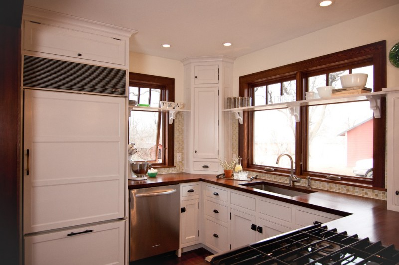 farmhouse kitchen idea in white with white upper corner cabinet glossy wood countertop white kitchen cabinets stainless steel appliances wood framed glass windows
