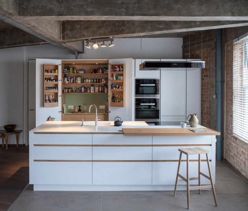 flat paneled cabinets in white wood interior shelves wood top kitchen island with white base wooden serving table single wooden bar stool an electric stove stainless steel appliances