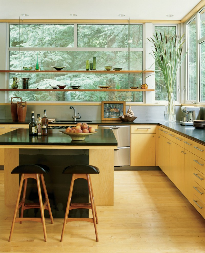 floating industrial kitchen shelves with a view L shape black countertop light toned lower cabinets black top island with wooden base a couple of bar stools stainless steel appliances