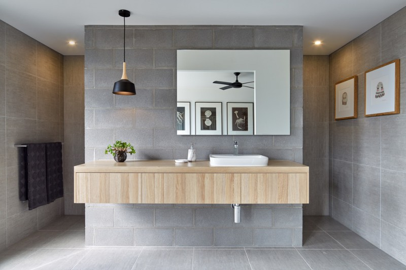 floating wood vanity with white sink and faucet frameless mirror grey tiles walls and floors