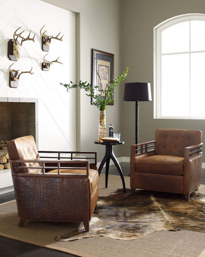 formal & personal living room a couple of leather chairs black finished round top table black standing lamp cowhide area rug white walls with animal head wall arts standard fireplace with stone suround