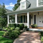 Front Porch And Lawn With Flower Beds Evergreen Shrubs Brick Pathways In Patterns Medium Colored Wooden Floors Patio White Doors And Fences