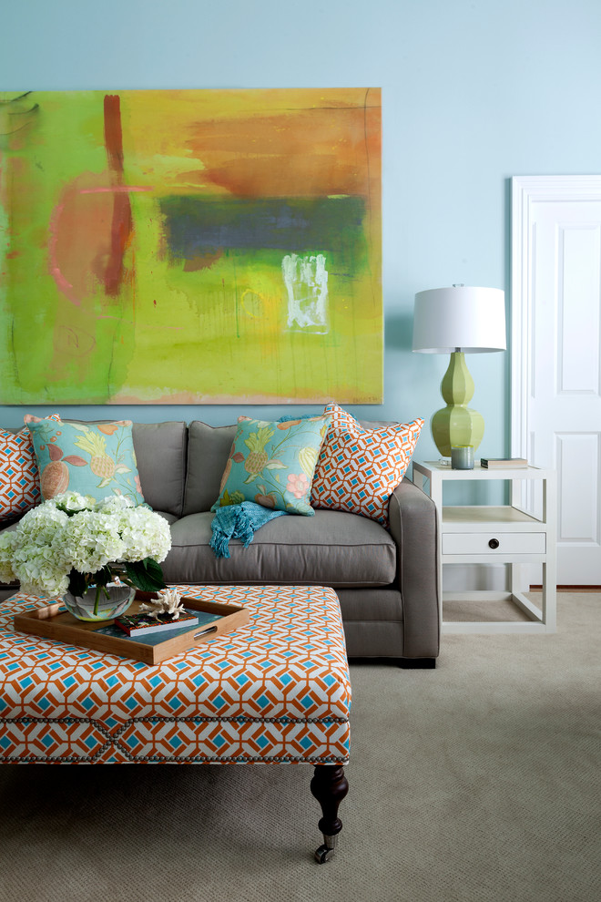 grey couch with multicolored accent pillows multicolored ottoman table grey area rug white side table with under shelves & drawer table lamp with green base abstract painting with strong colors
