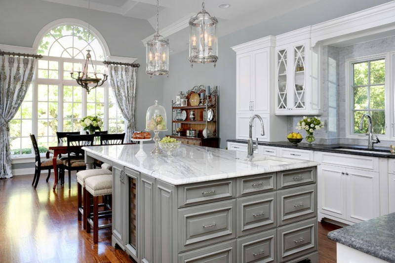 grey kitchen island with white marble top and storage on one side for wooden stools with white cushion
