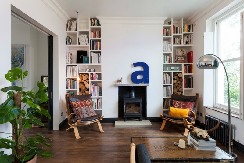 home library living room idea a couple of small chairs with accent pillows dark hardwood floors recessed book shelves with small fireplace at the center