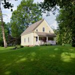 house plans for small homes grass field railing windows yellow walls roof trees farmhouse exterior