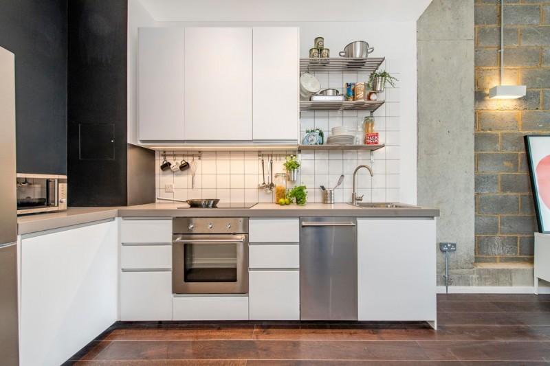 industrial kitchen concept with flat paneled cabinets in white lightweight metal shelving unit white ceramic tiles backsplash dark concrete walls dark toned floors stainless steel appliances