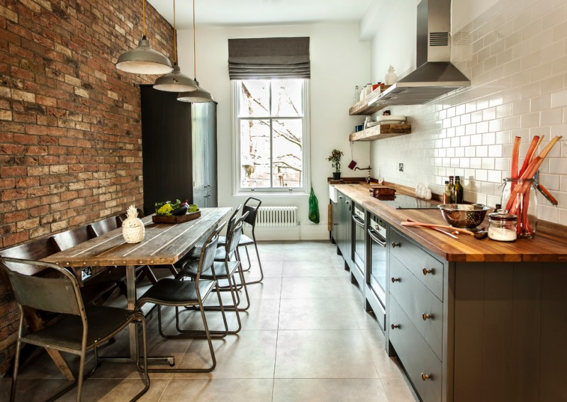 industrial kitchen shelves butcher block worktop white subway tiles walls red bricks walls stainless steel appliances dark toned wood dining table hardmetal dining chairs