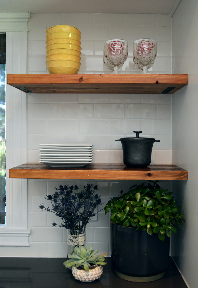 industrial kitchen shelves in between sink and fridge white ceramic subway tiles walls succulents decorative plates bowls and wine glasses
