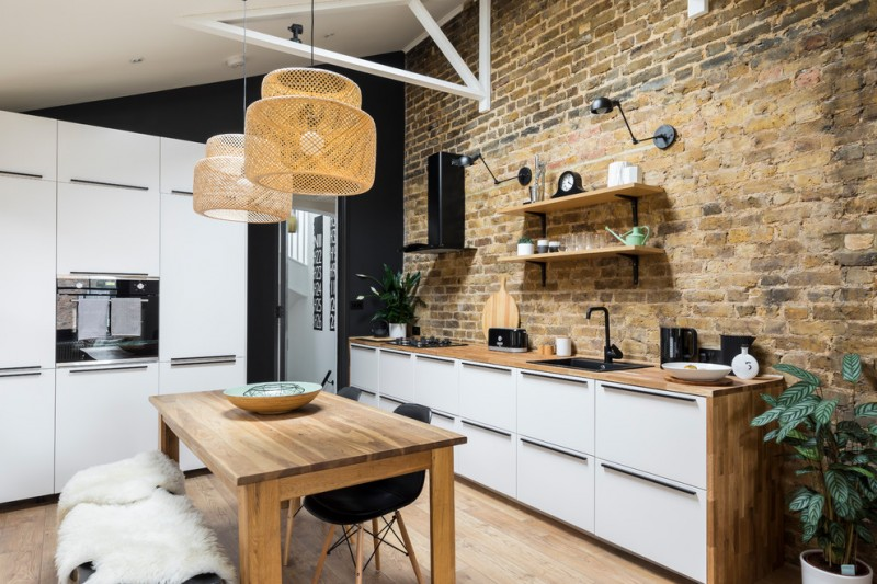 industrial kitchen with industrial shelving unit red brick walls wood countertop wood dining table with modern black chairs medium toned wood floors without finishing white recessed cabinets