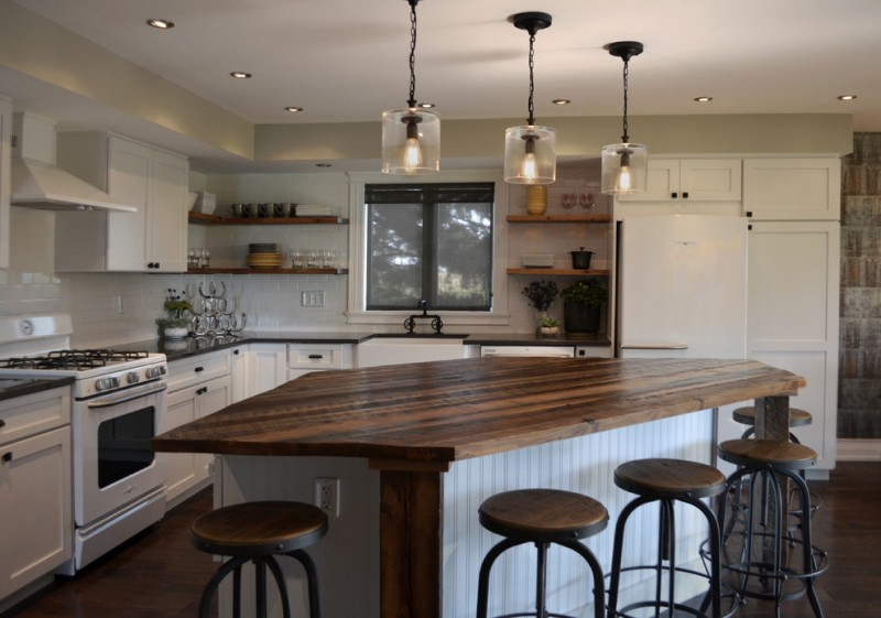 industrial kitchen with reclaimed wood bar table solid black countertop reclaimed wood open shelves white kitchen cabinets dark toned wood floors