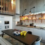 Industrial Kitchen With Wooden Kitchen Shelving Unit White Ceramic Tiles Backsplash Original Concrete Walls White Recessed Cabinets Solid Black Dining Table Modern Dining Chairs & Bench