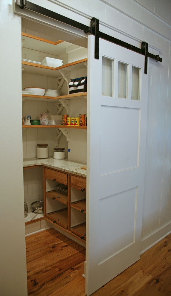 industrial pantry or kitchen shelving unit with white sliding barn door