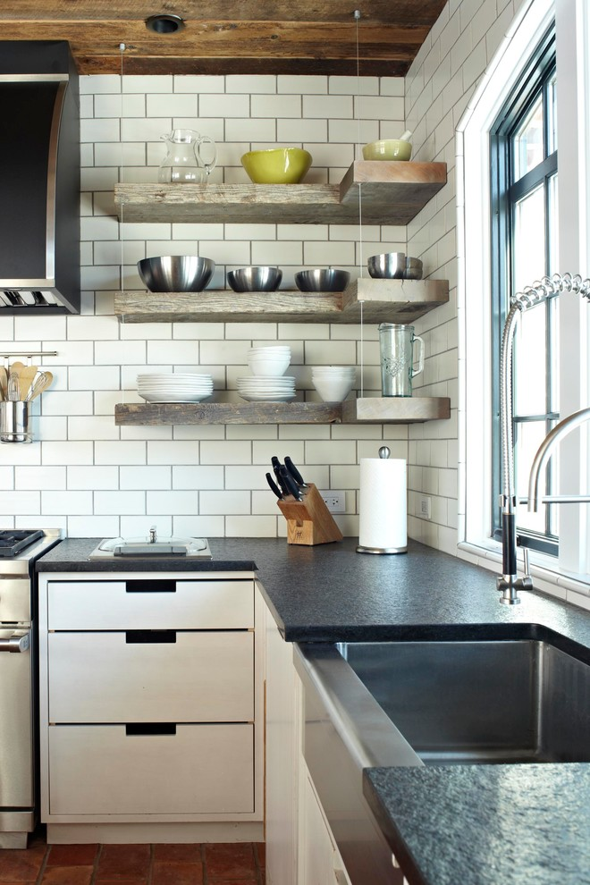 industrial wooden kitchen shelves supported by ceiling mounted wires white subway tiles backsplash black countertop flat panel kitchen cabinets in white undermount stainless steel sink and faucet