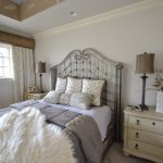 Iron Made Bed Frame With Classic Designed Headboard Light Cream Bedside Tables With Drawers White Bed Linen Grey Comforter Fluffy White Blanket