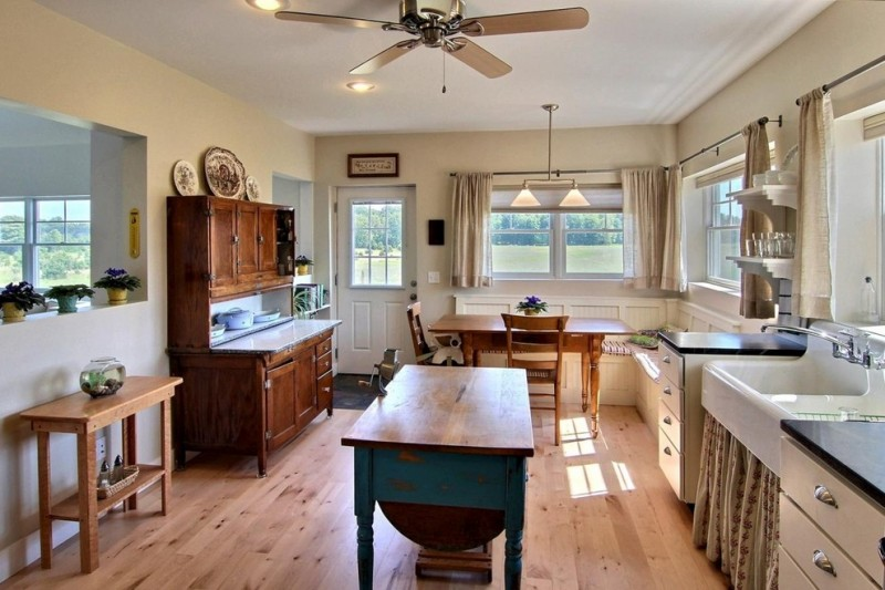 kitchen corner bench seating beautiful floor tables decorative plants windows curtains faucet sink ceiling fan lights chairs farmhouse room