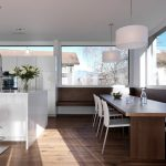 kitchen corner bench seating chairs table big windows flowers hanging lamps modern room