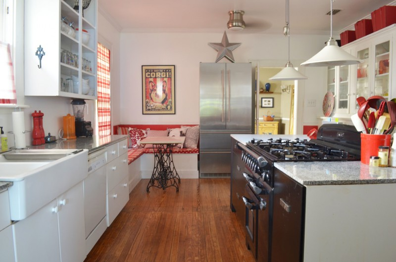 kitchen corner bench seating glass front wall cabinets fridge hanging lamps sink pillows stove table traditional room