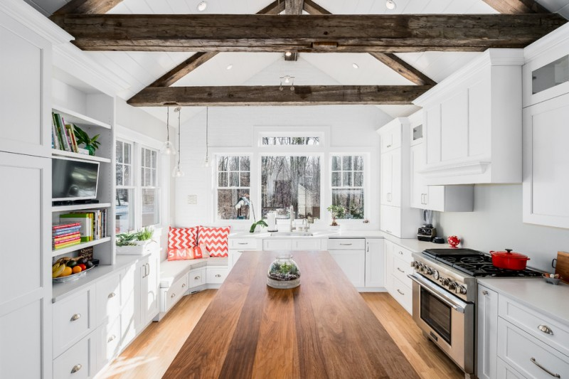 kitchen corner bench seating shelves books window wall cabinet stove beautiful floor pillows hanging lamps ceiling lights farmhouse room