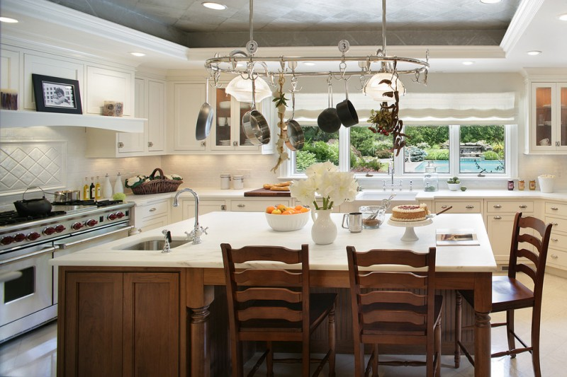 large kitchen island with white countertop, sink, three wooden chairs with backs, pot racks on top of the table with lamps on it