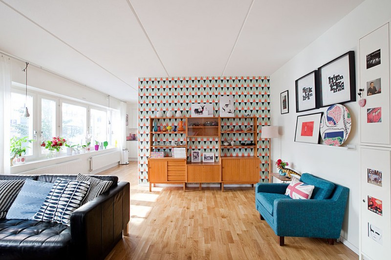 living room with pop colors bright blue couch white walls with wall arts wood rack multicolored wallpaper walls medium toned wood floors