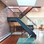 metal stair stringers brick wall upholstered chair hardwood floors glass railing treads ceiling lights modern design