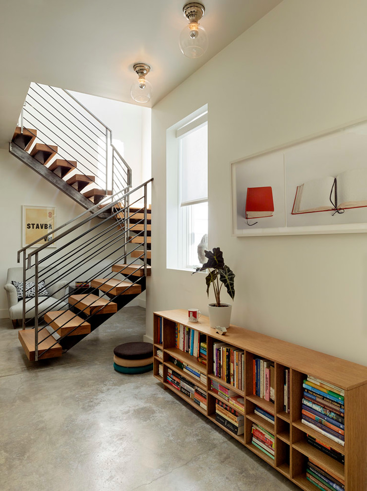 metal stair stringers marble floors armchair bookshelves window artwork pendants staircase contemporary design