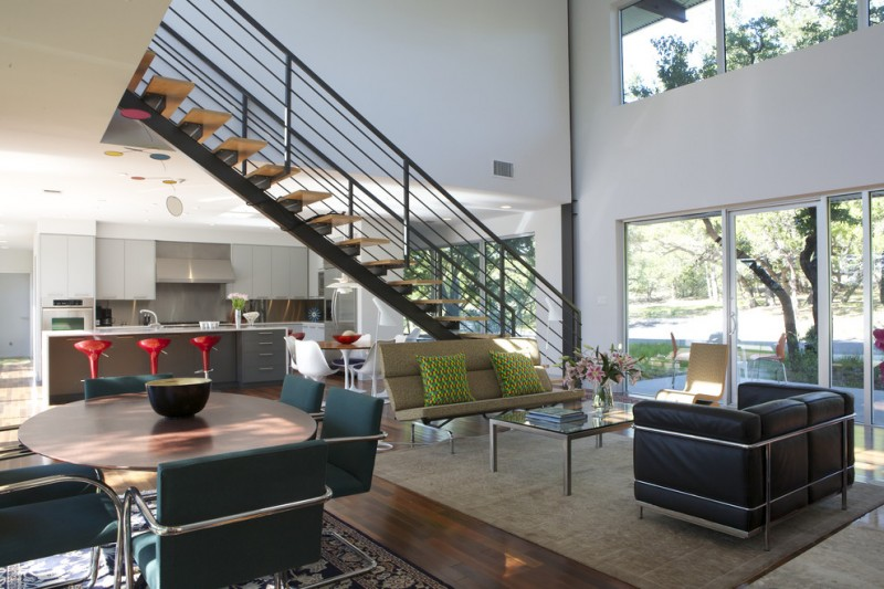 metal stair stringers staircase couches chairs table stools island white cabinets appliances hardwood floors carpet window walls modern design