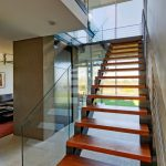 metal stair stringers staricase beige floors glass railing sofa window contemporary design