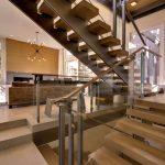 metal stair stringers wood treads beige floors glass railing sofa cabinet pendants ceiling lights contemporary design