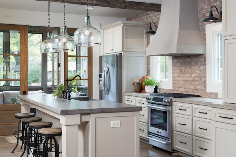 mid sized timeless kitchen with beige cabinets, granite countertops, stainless steel appliances, an island and recessed panel cabinets, glass pendant lights