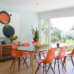 Midcentury Dining Set With Glass Top Table With Wooden Legs, Orange Sleek Chairs With Wooden Legs And Black Steel Support Under The Seating