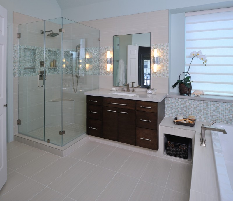 modern and clean bathroom walk in shower with transparent glass panels flat panel cabinets with white countertop frameless mirror with left right wall lamps mosaic walls white ceramic tiles floors