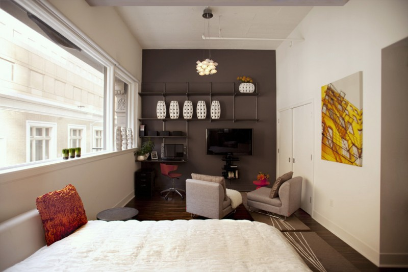 modern bedroom design a pair of sofa in beige wall mounted TV set small working chair in red wall mounted working desk integrated with shelves