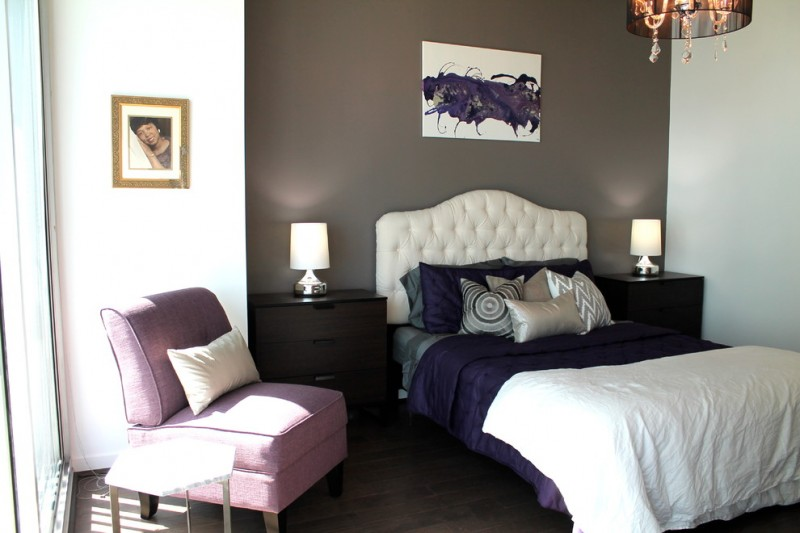 modern bedroom with queen bed frame with white tufted headboard bold blue bedding plus white blanket purple corner chair grey accent wall white walls dark toned wood floors