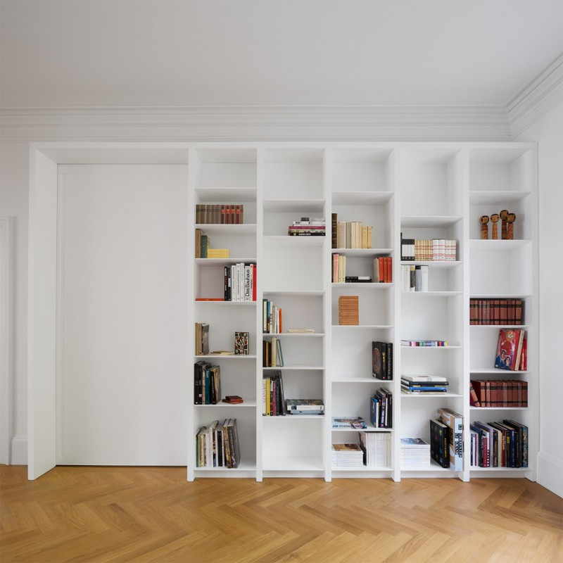 modern home library idea white bookshelves inserted in wall medium toned wood floors