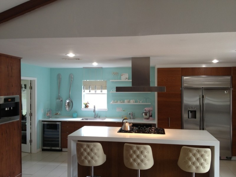 modern kitchen idea blue walls with display shelves in white white countertop wooden flat panel cabinets built in stainless steel appliances large kitchen island in white modern bar stools