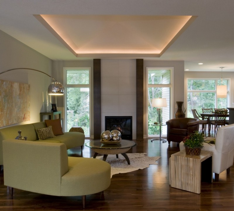 modern living room ideas geroge kovacs polished chrome arc floor lamp recessed lighting green couch glass and wood table fireplace