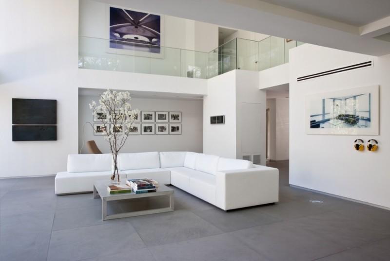 modern living room ideas limestone flooring rivolta sofa floral arrangement cocktail table decorative vase beige chair glass railing