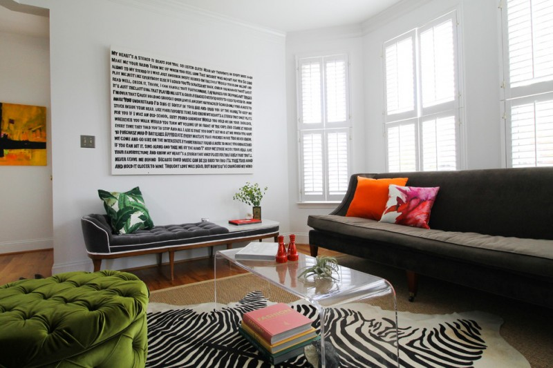 modern living room with three different single furniture animal printed area rug clear acrylic coffee table white walls with unique wall art