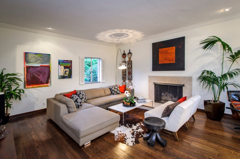 modern minimalist living room idea neutral colored sectional white sofa white top center table cowhide rug black finished side table dark hardwood floors