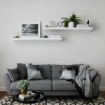 Modern Minimalist Living Room In Grey Grey Sofa With Accent Pillows And Blanket Wall Mounted Shelves In White Monochromatic Area Rug With Modern Patterns
