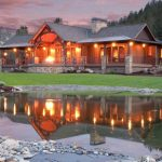 Mountain Style Exterior Home Design With Full Porch And Fences Entry Pillars And Gable Peak Trim Deck Wooden Walls