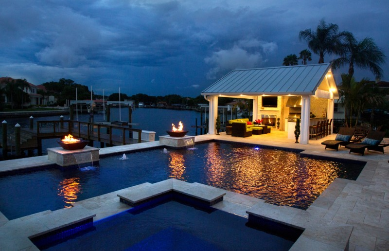 open pool house with kitchen, bar, TV, fireplace, couch set