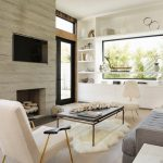Pale Toned Hardwood Floors Standard Fireplace With Wooden Panel Surround Recessed TV Set White Recessed Racks With Centered Glass Display Grey Couch Modern Black Center Table White Chair