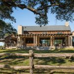 Ranch House Rustic Exterior House With Stone Walls And Exposed Mortar Glass Windows Wooden Fences Patio Table Sets